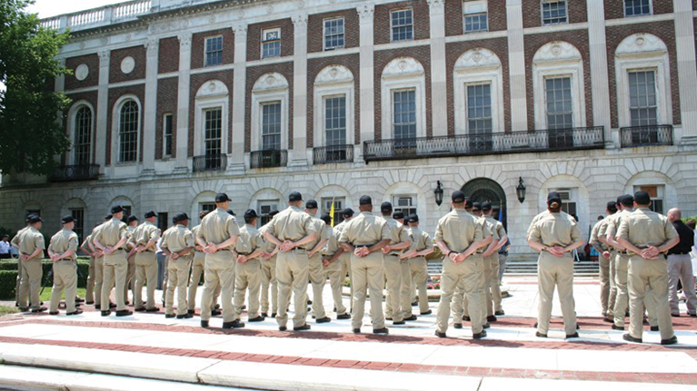 The Waterbury Police Academy in standing in front of Waterbury City Hall with their hands behind their backs