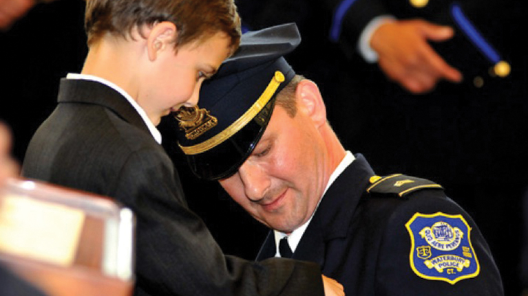 An officer receiving a pin from a child in an award ceremony