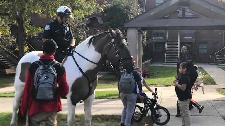 Group of neighborhood kids surround an officer mounted on a police horse